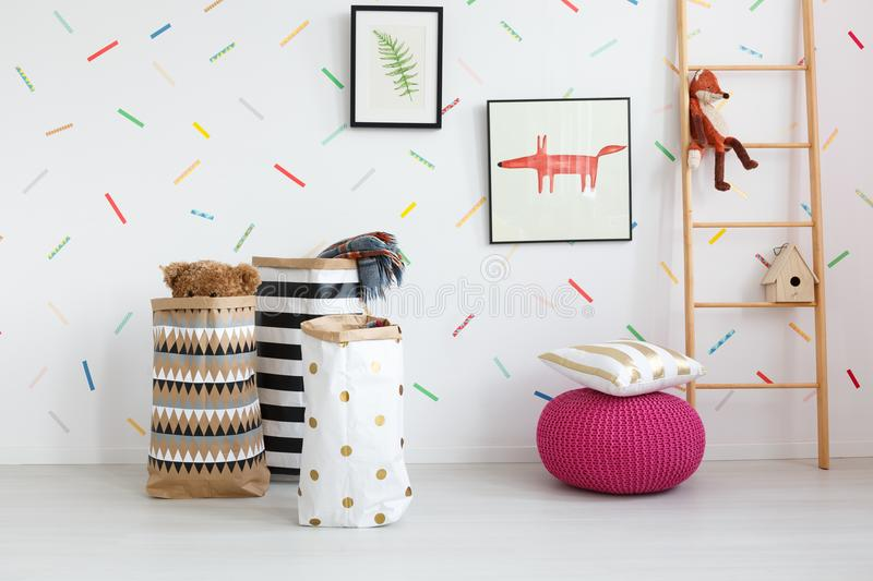 Ladder in cozy kid`s room. Patterned bags with toys next to pillow on pink pouf in cozy kid`s room with posters on wall royalty free stock image