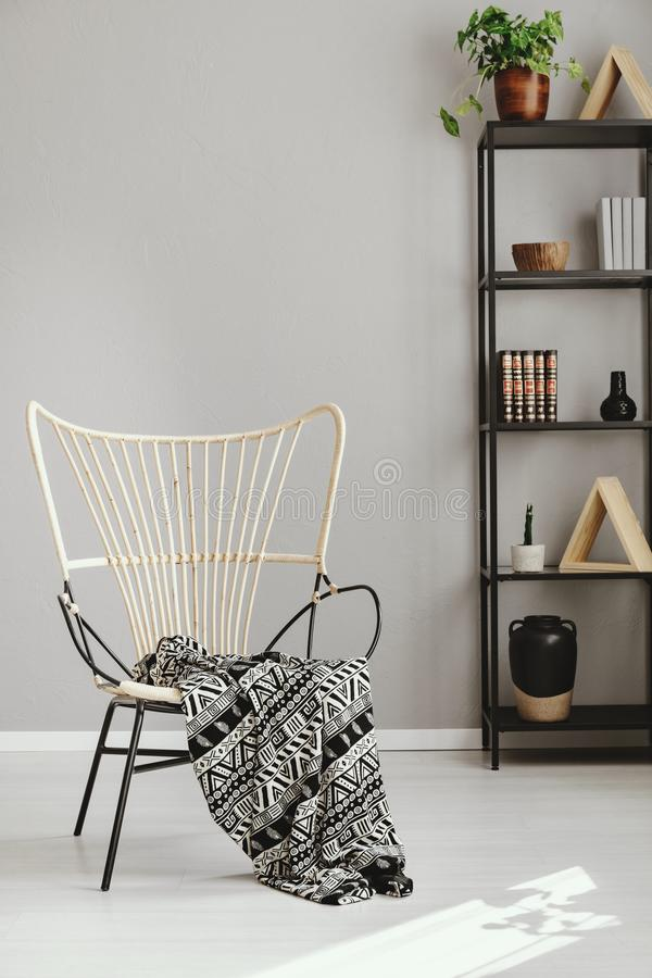 Patterned blanket on armchair in grey living room interior. Real photo royalty free stock photos