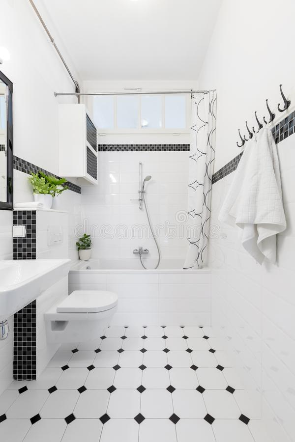 Patterned floor in white and black bathroom interior with towels. Toilet and bathtub. Real photo royalty free stock photos