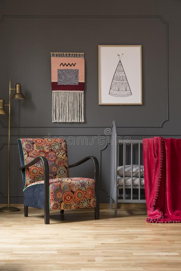 Patterned floral armchair next to baby`s bed in bedroom interior stock photography