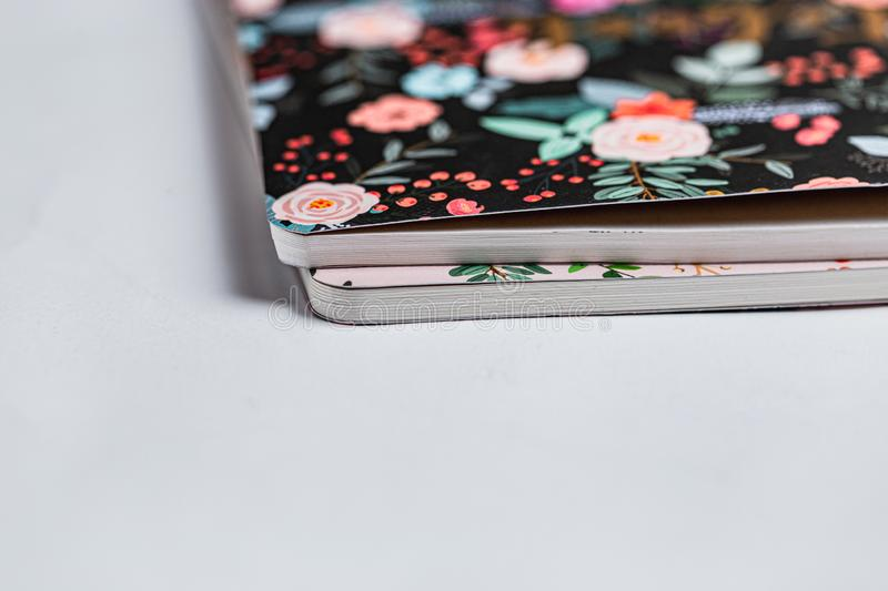 Patterned notebooks on white backdrop. Flower pattern on paper notebooks. Pink and black fancy girly things. Teenage girly pinky. Diary. Pink phone on white stock photo
