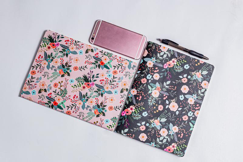 Patterned notebooks on white backdrop. Flower pattern on paper notebooks. Pink and black fancy girly things. Teenage girly pinky. Diary. Pink phone on white royalty free stock image