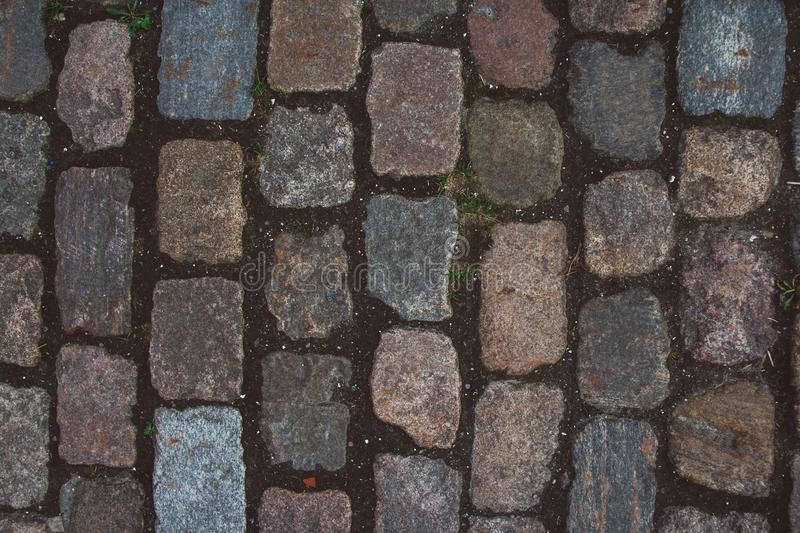 The texture of the old cobblestone and unusual stones. Patterned paving tiles cobblestone road for texture. Top view stock images