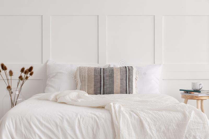 King size bed in white simple bedroom interior, real photo. Patterned pillow on the king size bed in white simple bedroom interior in elegant apartment, real royalty free stock photos