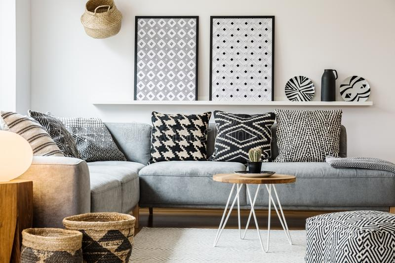 Patterned pillows on grey corner sofa in apartment royalty free stock photo