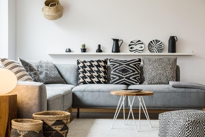 Patterned pillows on grey couch in modern living room interior w. Ith pouf and wooden table. Real photo stock photo