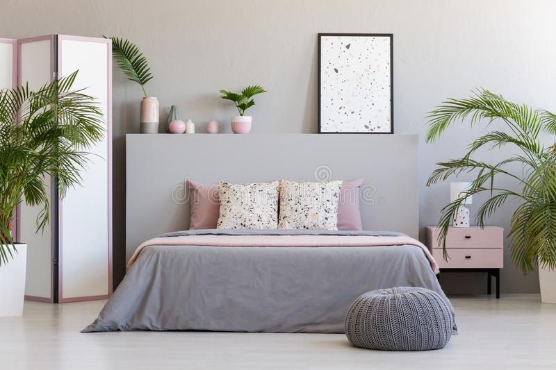 Patterned poster on grey headboard of bed with pillows in bedroom interior with pouf. Real photo stock photography