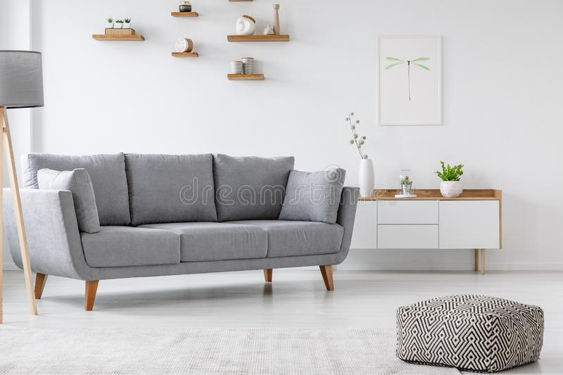 Patterned pouf and grey couch in minimal living room interior wi royalty free stock image