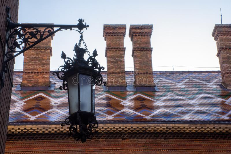 Patterned roof ornamented with multicolored tiles on the background and wall of a street lamp in the foreground. Architecture Univ royalty free stock photography