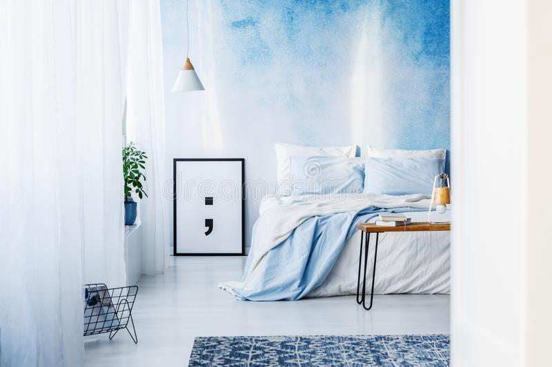 Patterned rug and poster in blue bedroom interior with bed again royalty free stock image