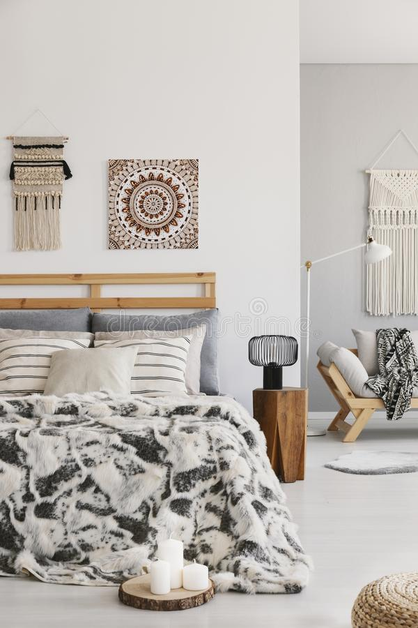 Patterned sheets on bed next to lamp on wooden stool in bedroom interior with poster. Real photo stock photo