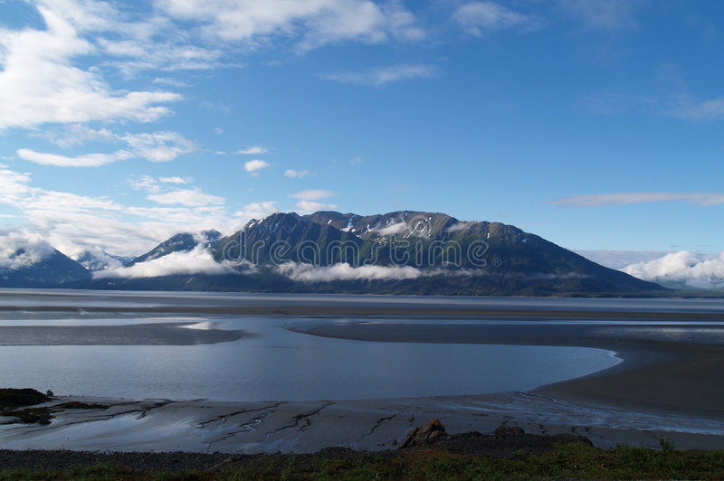 Patterns; low tide and mountains backdrop. stock photo