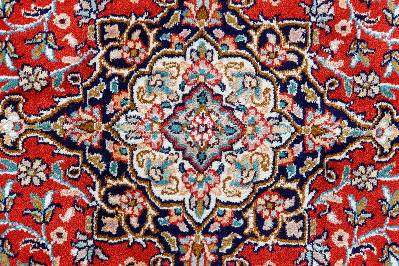 Detail of oriental carpet pattern. Patterns on a red decorated carpet from the orient, the background of the image forms a pattern of oriental carpet royalty free stock photography