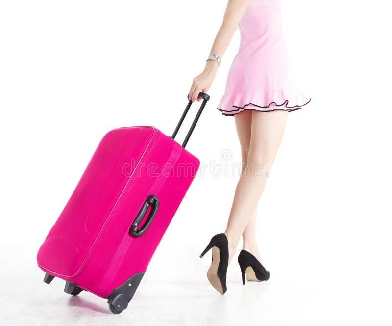 Pattes de femme allant et tirant la valise de vacances photographie stock libre de droits