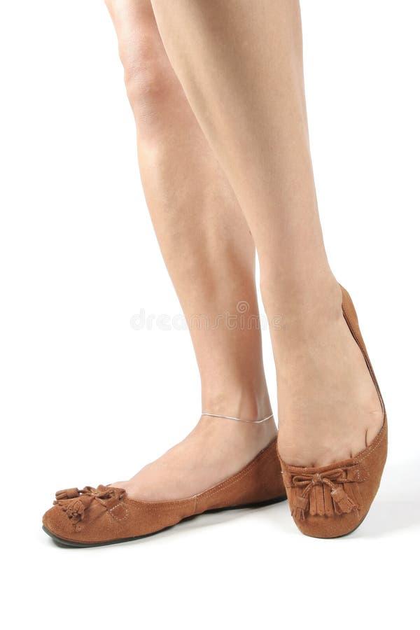 Pattes de femme avec les chaussures brunes photo stock