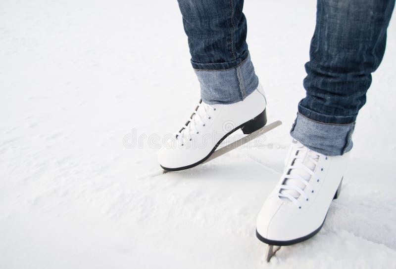 Pattes de femme dans les patins de glace blancs image libre de droits