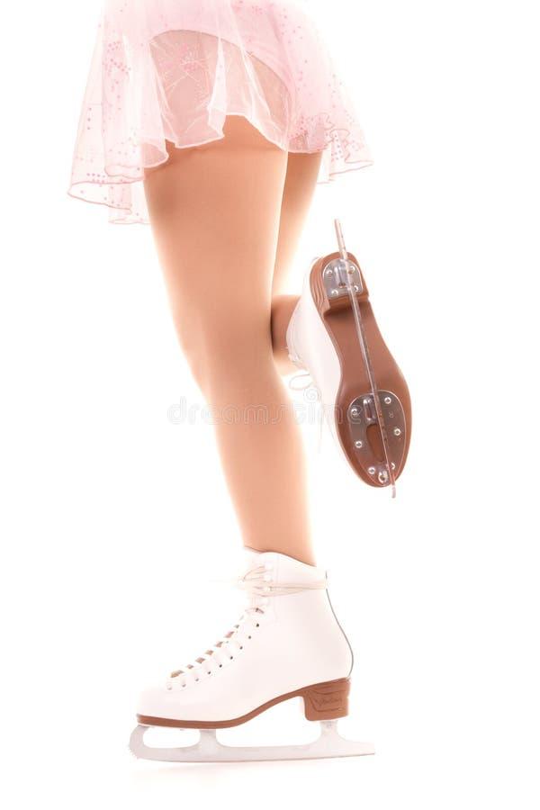 Pattes de femme dans les patins de glace blancs image stock
