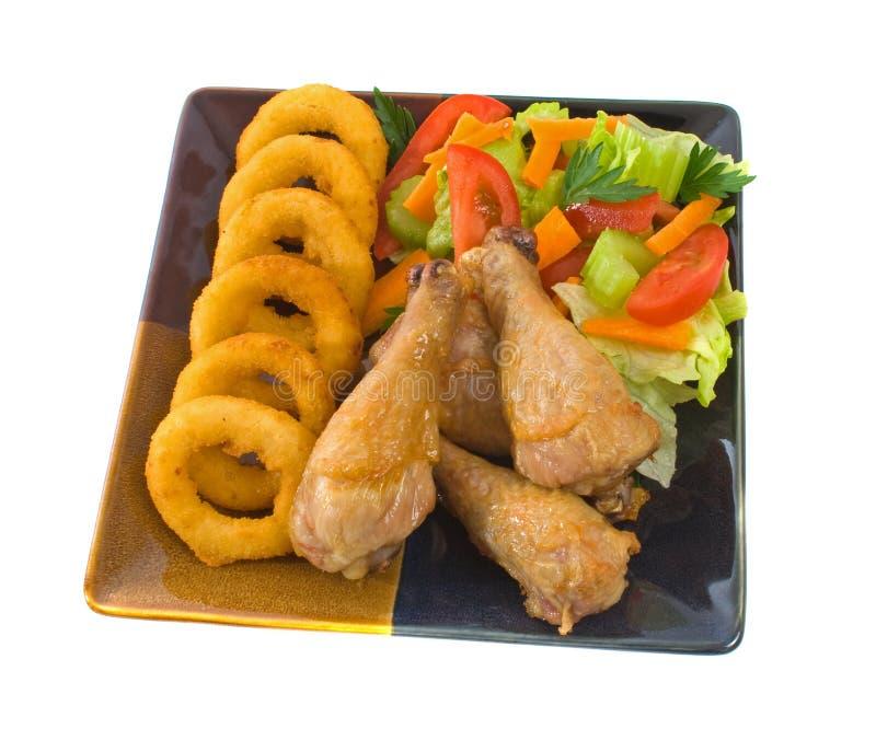 Pattes de poulet rôti avec des boucles d'oignon images stock