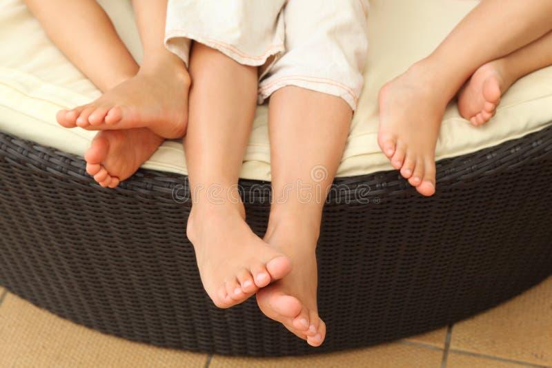 Pattes des enfants aux pieds nus se trouvant sur le sofa photos stock