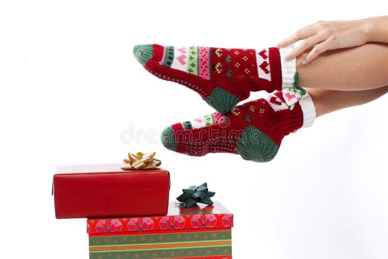 Pattes femelles dans des bas de Noël d'isolement sur le whi photographie stock
