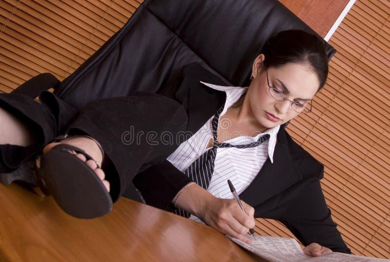 Pattes financières de femme d'affaires sur le bureau photographie stock
