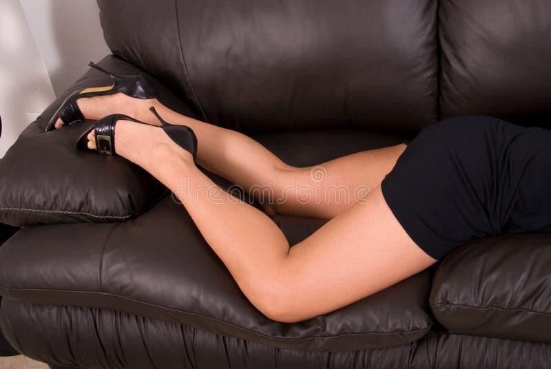Pattes sexy sur le sofa en cuir. photographie stock libre de droits