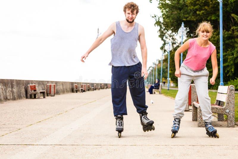 Pattinaggio a rotelle attivo degli amici dei giovani all'aperto immagine stock