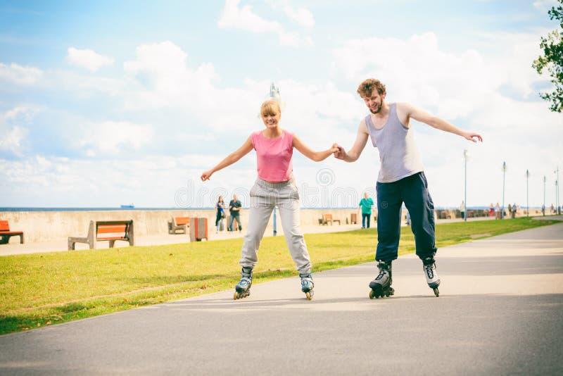 Pattinaggio a rotelle attivo degli amici dei giovani all'aperto fotografia stock