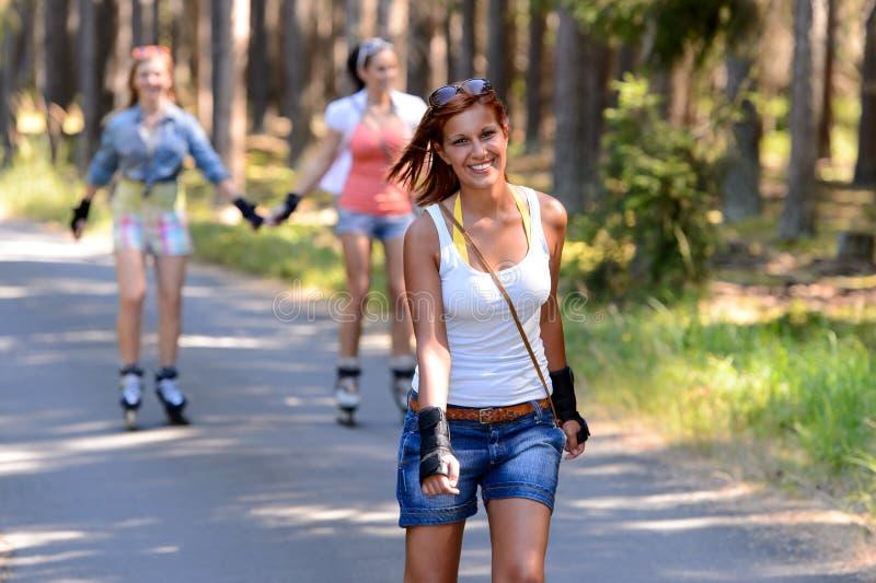 Pattinaggio a rotelle della giovane donna all'aperto con gli amici fotografia stock libera da diritti
