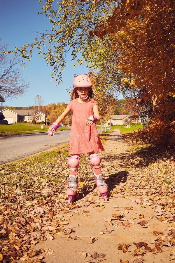 Pattinaggio a rotelle sorridente della bambina nel parco di autunno fotografia stock libera da diritti
