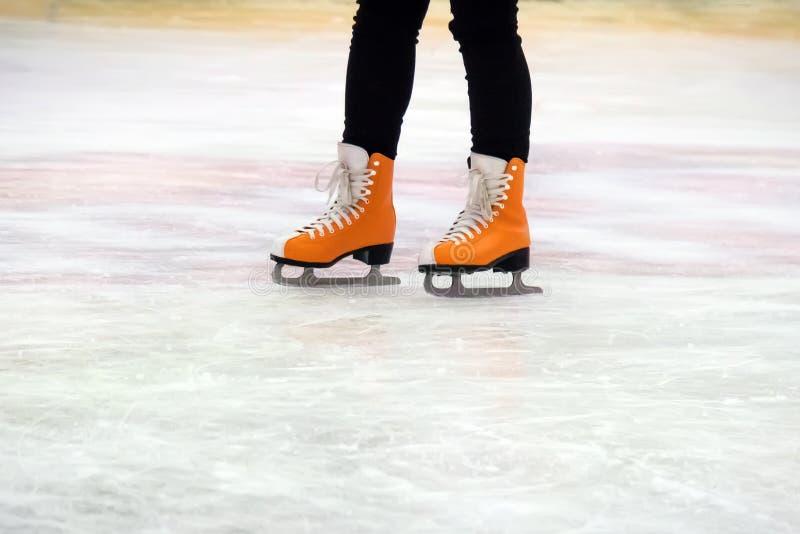 Pattinaggio su ghiaccio della donna inverno all'aperto sulla pista di pattinaggio sul ghiaccio ghiaccio e gambe fotografia stock
