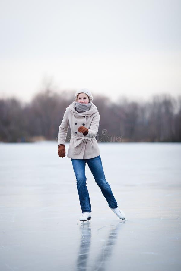 Pattinaggio su ghiaccio della giovane donna all'aperto su uno stagno immagini stock libere da diritti