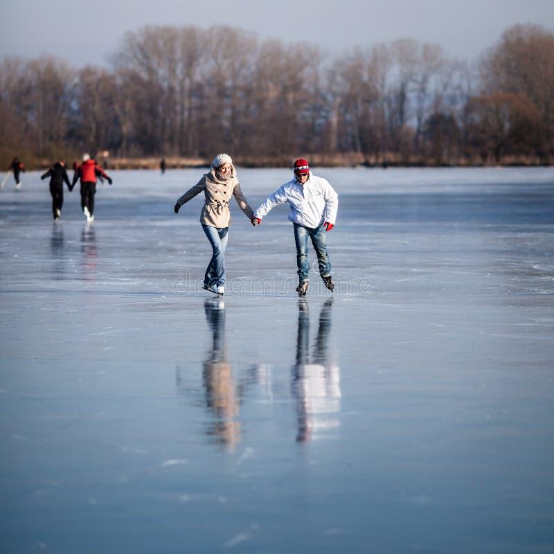 Pattinaggio su ghiaccio delle coppie all'aperto su uno stagno fotografia stock