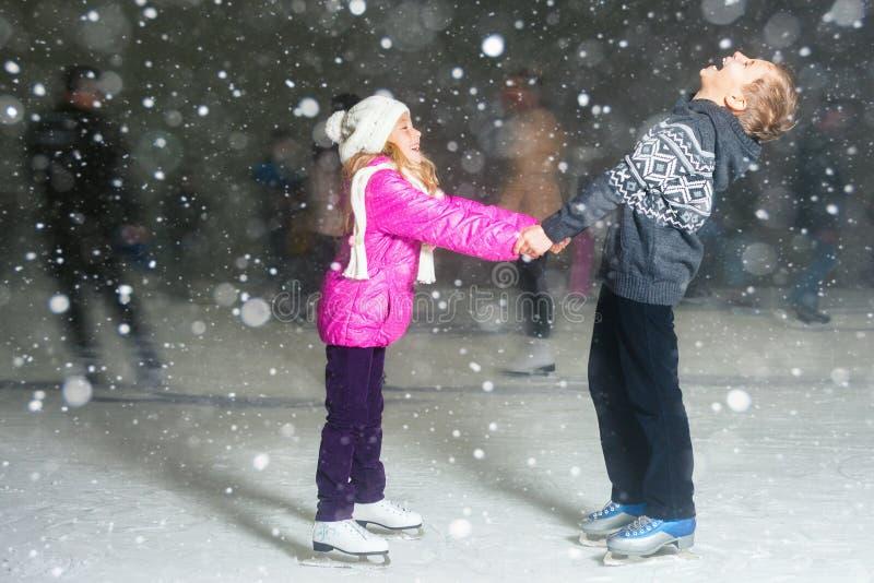 Pattinaggio su ghiaccio felice alla pista di pattinaggio sul ghiaccio, notte dei bambini di inverno fotografia stock