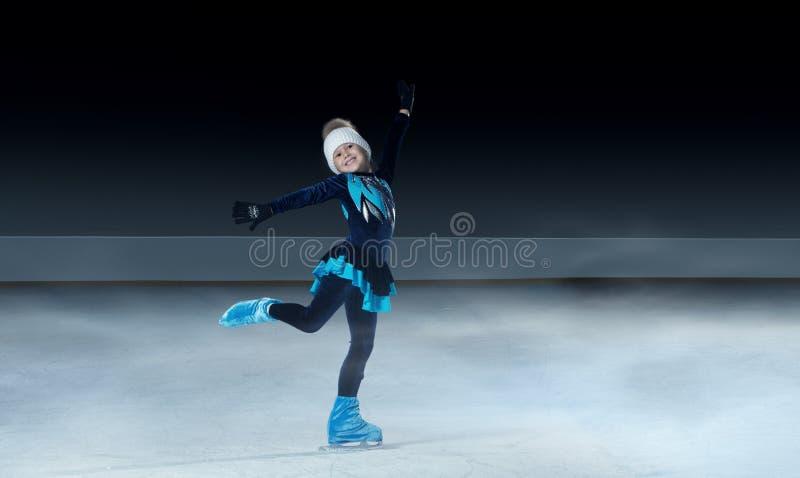 Pattinatore artistico sul fondo scuro dell'arena del ghiaccio fotografia stock