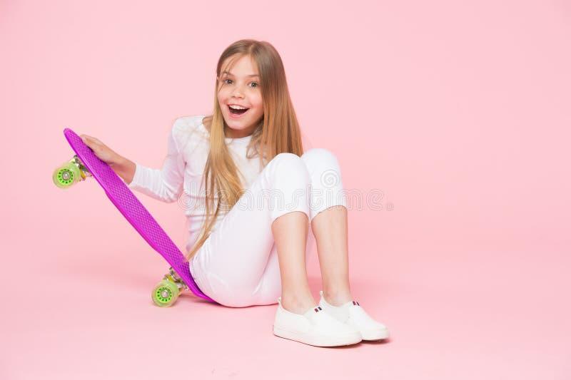 Pattinatore del bambino che sorride con il longboard Il bambino del pattino si siede sul pavimento Piccolo sorriso della ragazza  immagini stock libere da diritti