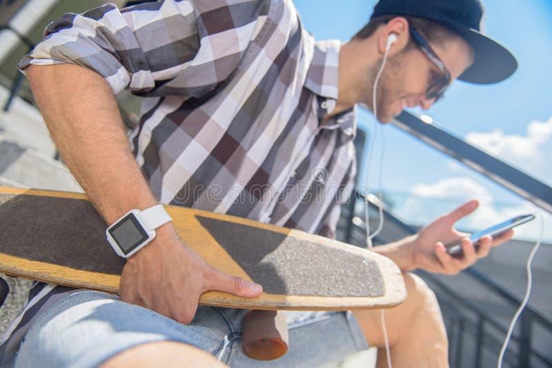 Pattinatore maschio allegro che intrattiene con il telefono fotografia stock libera da diritti