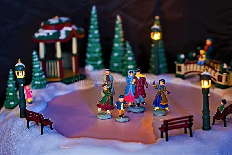 Pattinatori miniatura di inverno con fondo scuro fotografie stock