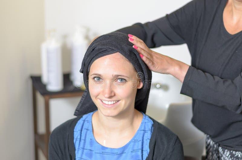Patting парикмахера сушит волосы молодой женщины стоковые изображения