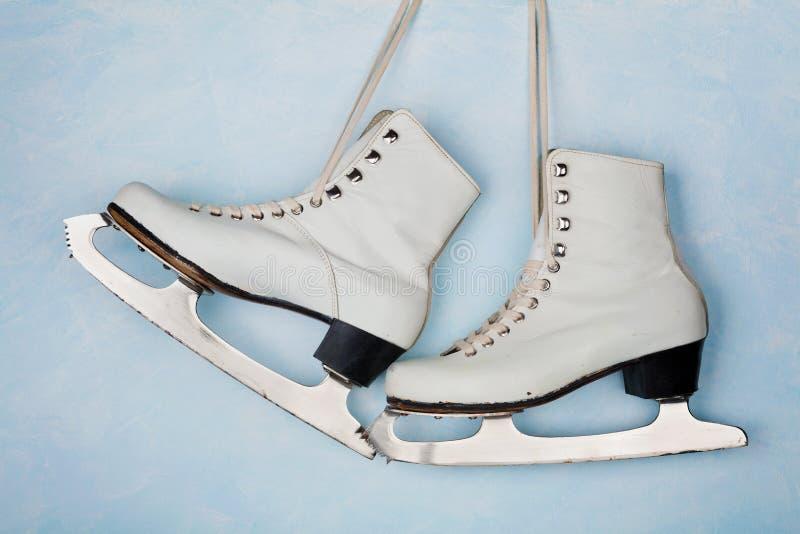 Pattini da ghiaccio d'annata per il pattinaggio artistico che appende sui precedenti della parete blu fotografia stock