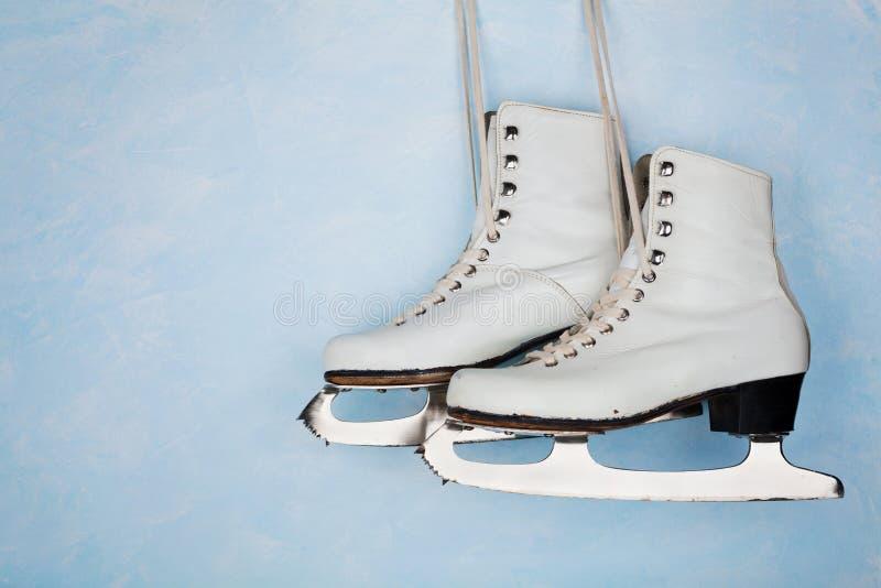 Pattini da ghiaccio d'annata per il pattinaggio artistico che appende sui precedenti della parete rustica blu immagini stock libere da diritti