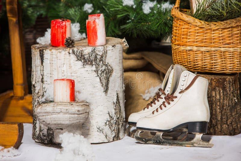 Pattini da ghiaccio d'annata per il pattinaggio artistico con il ramo di albero dell'abete che appende sul fondo rustico fotografie stock libere da diritti