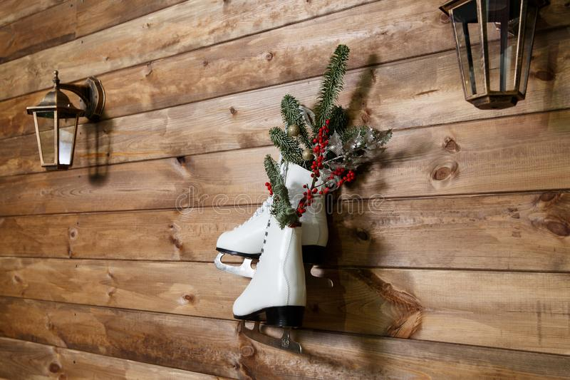 Pattini da ghiaccio d'annata per il pattinaggio artistico con il ramo di albero dell'abete che appende sul fondo rustico fotografia stock libera da diritti