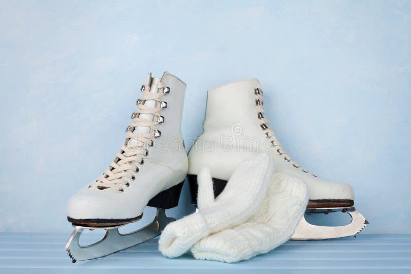 Pattini da ghiaccio d'annata per il pattinaggio artistico e guanti tricottati sul fondo del turchese fotografia stock
