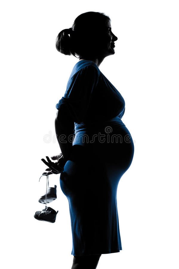 Pattini di bambino della holding del ritratto della donna incinta immagini stock