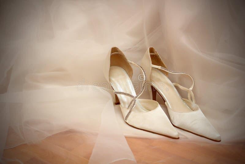 Pattini di cerimonia nuziale sul vestito nuziale bianco. fotografia stock libera da diritti