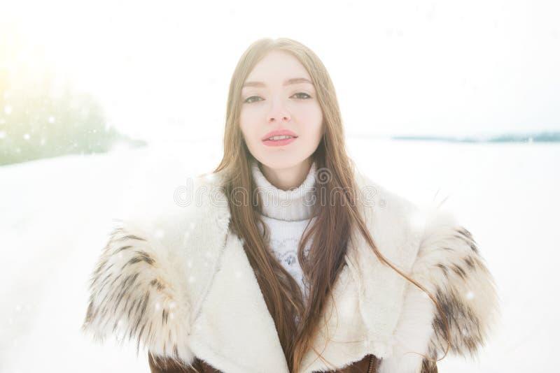 Pattini di ghiaccio della holding della donna di inverno pattinare di ghiaccio all'aperto in neve Bella giovane donna caucasica c fotografie stock libere da diritti