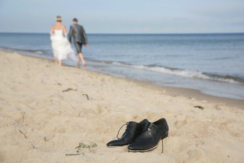 Pattini di Groom sulla spiaggia fotografia stock