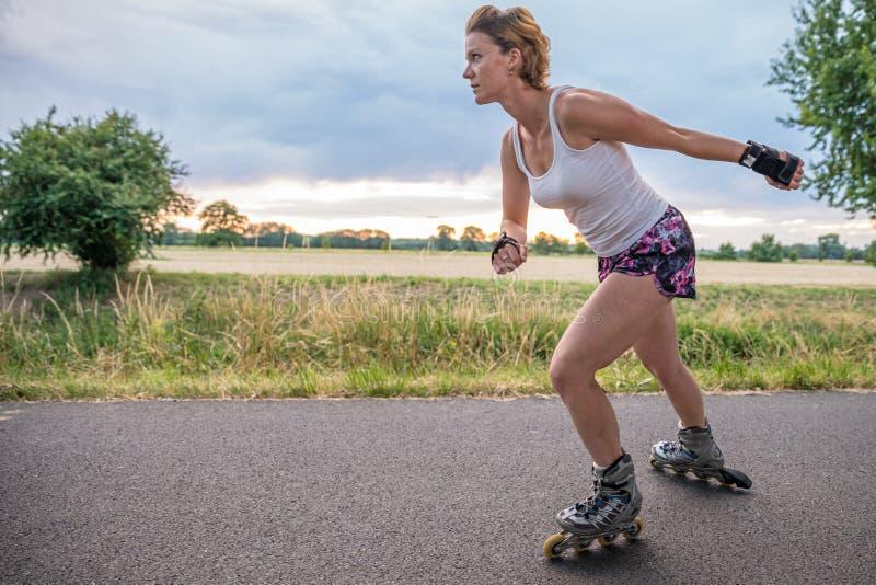 Pattini di rullo nell'azione sulla traccia dell'asfalto alle corse di stile libero fuori della città fotografia stock