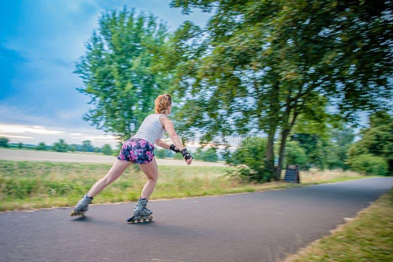 Pattini di rullo nell'azione sulla traccia dell'asfalto alle corse di stile libero fuori della città immagine stock
